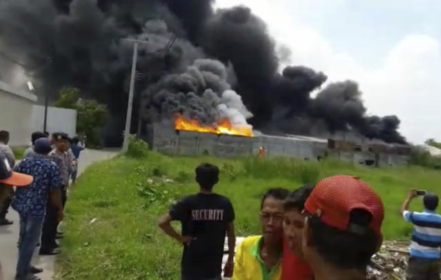 <p>In this image made from video, residents watch as thick black smoke billows from the site of an explosion at a firecracker factory in Tangerang, on the outskirt of Jakarta, Indonesia, Thursday, Oct. 26, 2017. (Photo: AP) </p>