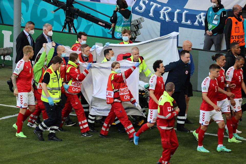 Players escort paramedics as Denmark's midfielder Christian Eriksen is evacuated from the pitch during the UEFA EURO 2020 Group B football match between Denmark and Finland at the Parken Stadium in Copenhagen on June 12, 2021. (Photo by WOLFGANG RATTAY / POOL / AFP) (Photo by WOLFGANG RATTAY/POOL/AFP via Getty Images)