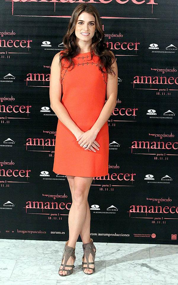 """But the actress has been turning heads all over Europe while promoting  """"The Twilight Saga: Breaking Dawn -- Part 1."""" At a fan event, Nikki popped a rather demure pose in a bright orange Michael Kors dress featuring stitched detailing around the neckline. Loose locks, sexy suede sandals, and her sparkling wedding ring completed the flawless look. (10/28/2011)"""