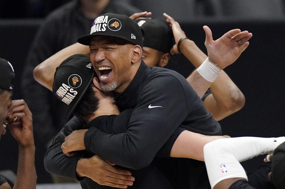 Phoenix Suns head coach Monty Williams, right, hugs Dario Saric after they won Game 6 of the NBA basketball Western Conference Finals against the Los Angeles Clippers Wednesday, June 30, 2021, in Los Angeles. The Suns won the game 130-103 to take the series 4-2. (AP Photo/Mark J. Terrill)