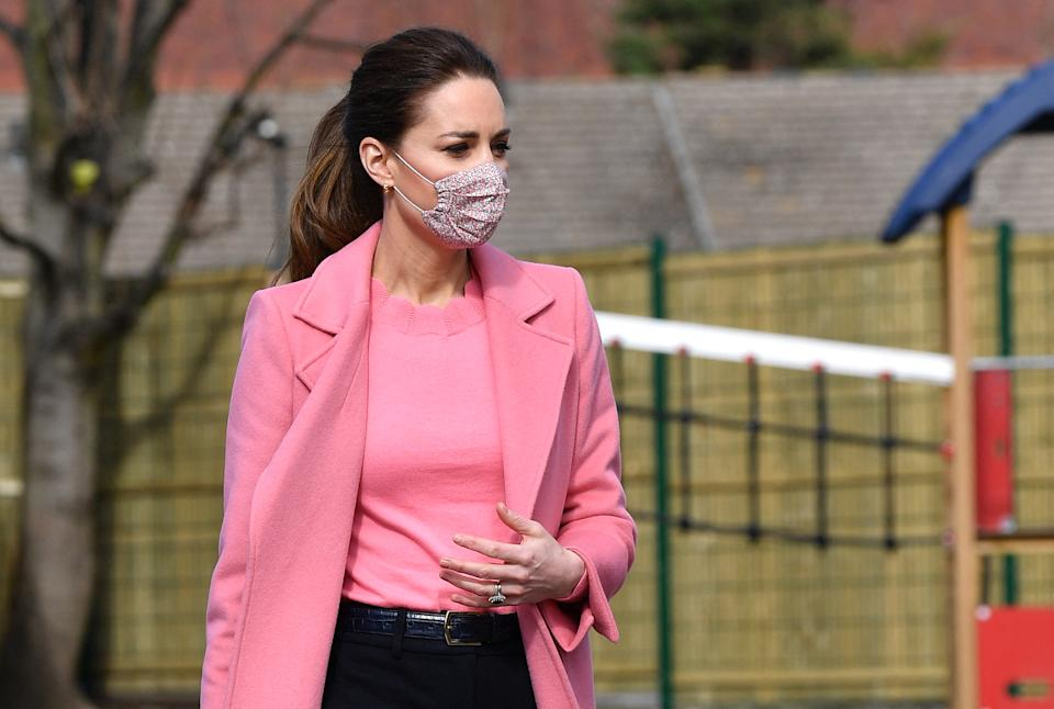 The Duchess of Cambridge opted for a matching bright pink jumper and coat, pink floral face covering, as well as black flare trousers and chain hoop earrings. (Getty Images)