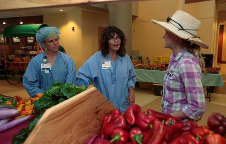 Amanda Sweetman, project manager, The Farm, talks with two Registered Nurses about the fresh vegetables for sale in the main lobby at Saint Joseph Mercy hospital in Ypsilanti, Michigan, U.S., August 23, 2017. Picture taken august 23, 2017. REUTERS/Rebecca Cook