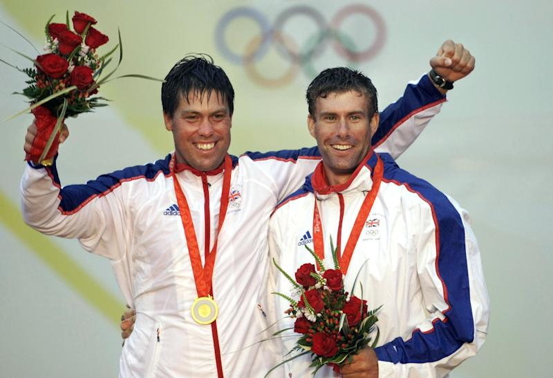 FILE - In this Aug. 21, 2008, file photo, Britain's Iain Percy, right, and Andrew Simpson, smile during the medal ceremony of the Star class sailing competition of the Beijing Olympics in Qingdao, China. They won the gold medal. Artemis Racing says Simpson died Thursday, May 9, 2013, after the team's boat capsized during training for the upcoming America's Cup in San Francisco Bay. (AP Photo/Herbert Knosowski, File)