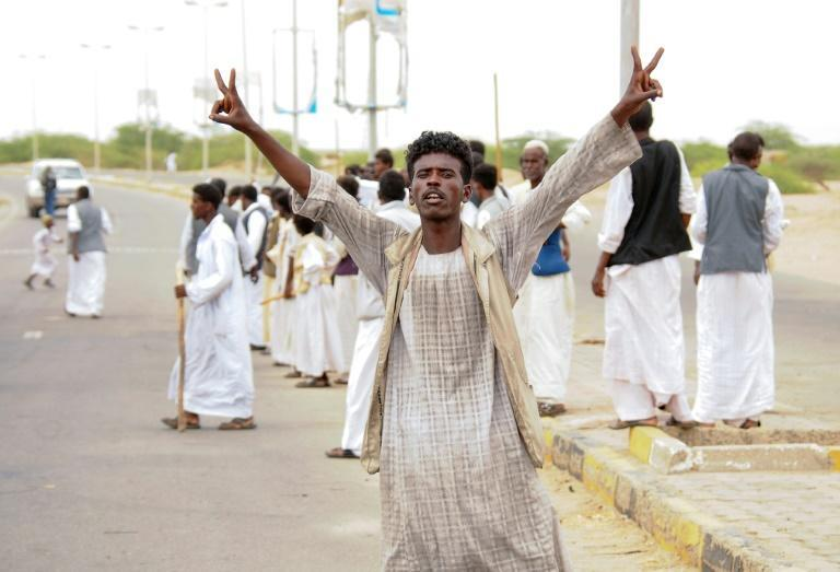 A protester flashes victory signs following the arrival in Port Sudan of a delegation led by a member of Sudan's ruling Sovereign Council on September 26, 2021 (AFP/Ibrahim ISHAQ)