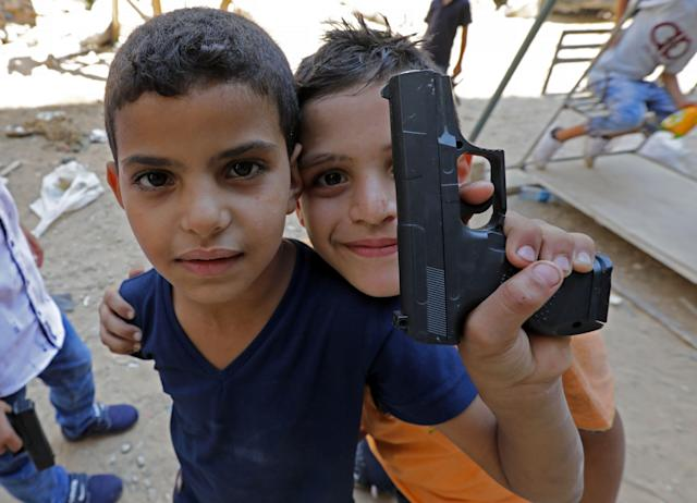 <p>Syrian refugee children poses for a photo as they play on a street in the Palestinian Shatila refugee camp, on the southern outskirts of the Lebanese capital Beirut, on Sept. 1, 2017, as Muslims mark the first day of the Eid al-Adha holiday. (Photo: Anwar Amro/AFP/Getty Images) </p>