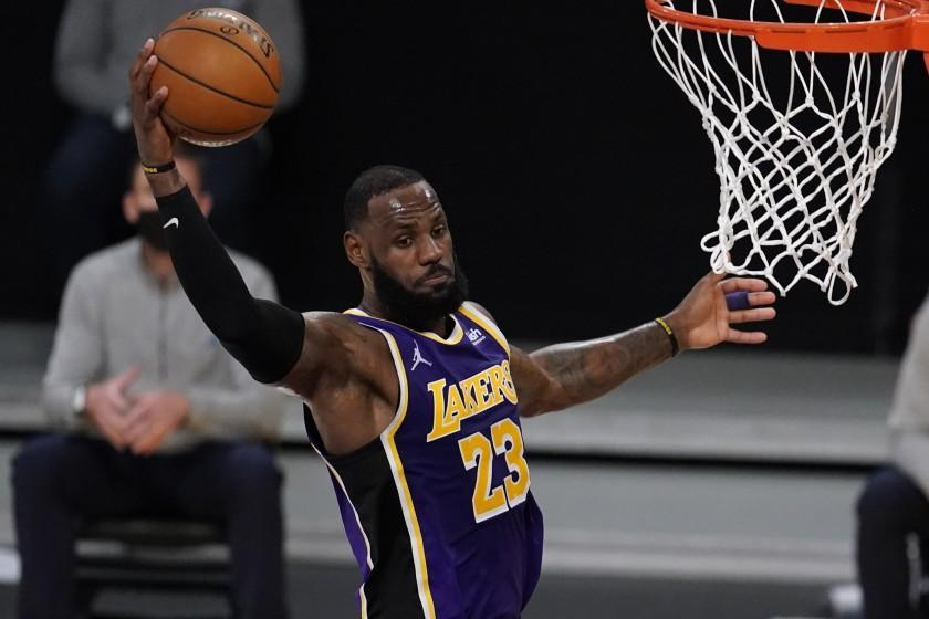 Los Angeles Lakers forward LeBron James grabs a rebound against the Charlotte Hornets during the first half of an NBA basketball game Thursday, March 18, 2021, in Los Angeles. (AP Photo/Marcio Jose Sanchez)