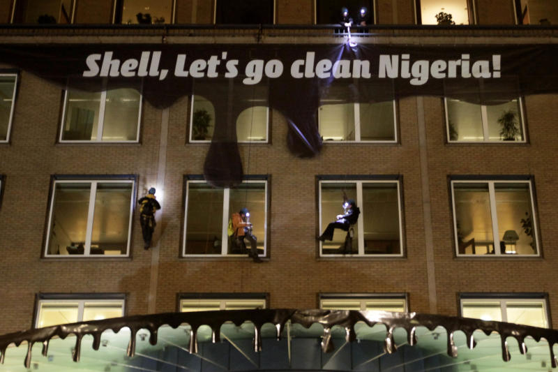 Activists from Milieudefensie, the Dutch arm of the Friends of the Earth environmental organization, attach a banner and plastic made to look like dripping oil, to the Shell headquarters in The Hague, Netherlands, Wednesday Jan. 26, 2011. A Dutch parliamentary commission is meeting with Shell and environmental groups today to discuss business development in West Africa. (AP Photo/Peter Dejong)