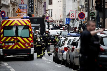 French police and firefighters secure the street as a man has taken two people hostage at a business in Paris France