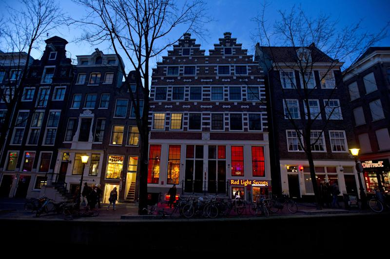In this photo taken Tuesday, Feb. 4, 2014, the entrance of the 'Red Light Secrets' prostitution museum is seen, center, in Amsterdam. On any given evening, thousands of tourists stroll down the narrow streets of Amsterdam's famed Red Light District, gawking at ladies in lingerie who work behind windows, making a living selling sex for money. Now a small educational museum is opening in heart of the district that aims to show reality from the other side of the glass. Organizer Melcher de Wind says the Red Light Secrets museum is for those who want to learn more about how the area works without actually visiting a prostitute. (AP Photo/Evert Elzinga)