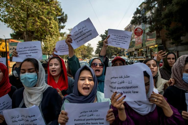 About a dozen Afghan women protested briefly Sunday outside the old Ministry for Women's Affairs, which has now been replaced by a department that earned notoriety for enforcing strict islamic doctrine (AFP/BULENT KILIC)