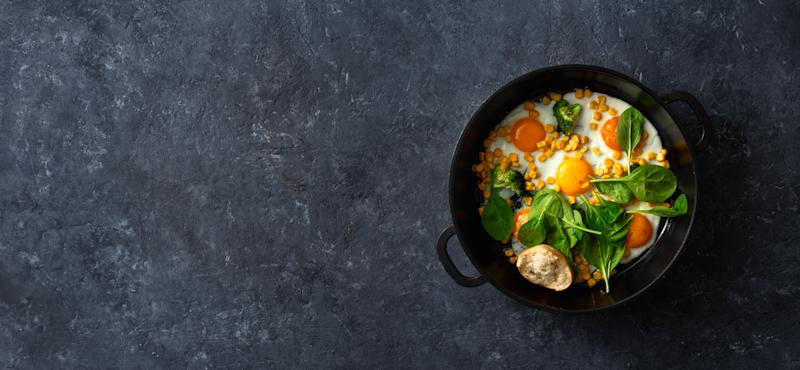 Healthy breakfast table with fry pan eggs with spinach and corn on dark stone background top view