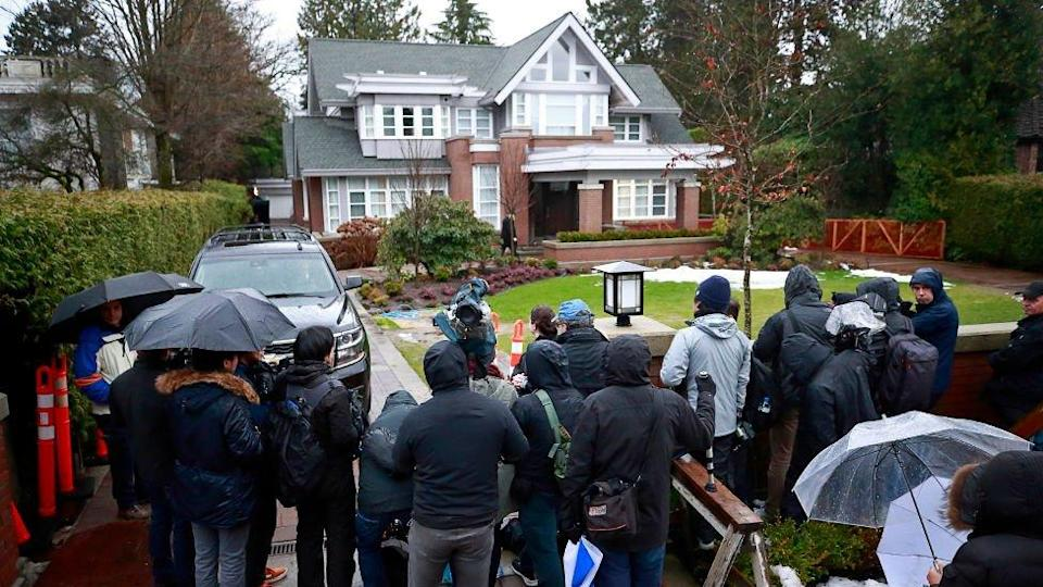 Media stand outside the home of Meng Wanzhou as they wait for her to leave for a court appearance in Vancouver