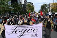 "People hold a ""Justice for Joyce"" sign during a demonstration in Montreal on October 3 2020, to demand action for the death of Joyce Echaquan, a Canadian indigenous woman subjected to live-streamed racist slurs by hospital staff before her death"