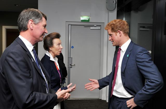LONDON, ENGLAND - JULY 27: Prince Harry speaks with Princess Anne, the Princess Royal and her husband Timothy Laurence as they arrive for the Olympic Games 2012 Opening Ceremony on July 27, 2012 in London, England. Athletes, heads of state and dignitaries from around the world have gathered in the Olympic Stadium for the opening ceremony of the 30th Olympiad. London plays host to the 2012 Olympic Games which will see 26 sports contested by 10,500 athletes over 17 days of competition. (Photo by John Stillwell - WPA Pool/Getty Images)