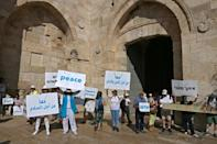 Israeli women peace activists take part in a rally calling for coexistence and an end to the Israeli-Palestinian conflict, along Jerusalem's Old City walls, on May 19, 2021