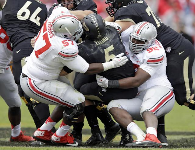 Purdue quarterback Danny Etling, center, is sacked by Ohio State defensive lineman Adolphus Washington, right and Chase Farris during the second half of an NCAA college football game in West Lafayette, Ind., Saturday, Nov. 2, 2013. Ohio State defeated Purdue 56-0. (AP Photo/Michael Conroy)