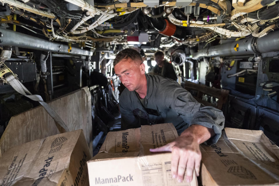 """U.S. Marine Corps Lance Cpl. Brandon Oldham, unloads food from a VM-22 Osprey at Jeremie Airport, Saturday, Aug. 28, 2021, in Jeremie, Haiti. The VMM-266, """"Fighting Griffins,"""" from Marine Corps Air Station New River, from Jacksonville, N.C., are flying in support of Joint Task Force Haiti after a 7.2 magnitude earthquake on Aug. 22, caused heavy damage to the country. (AP Photo/Alex Brandon)"""