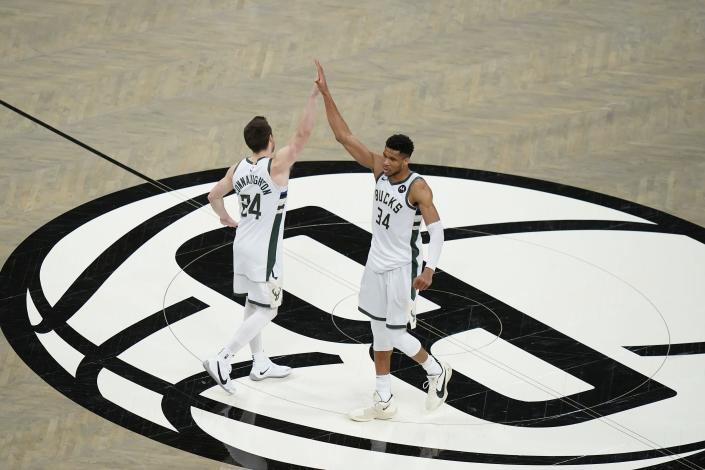 Milwaukee Bucks' Giannis Antetokounmpo (34) celebrates wth Pat Connaughton (24) after Game 7 of a second-round NBA basketball playoff series against the Brooklyn Nets, Saturday, June 19, 2021, in New York. (AP Photo/Frank Franklin II)