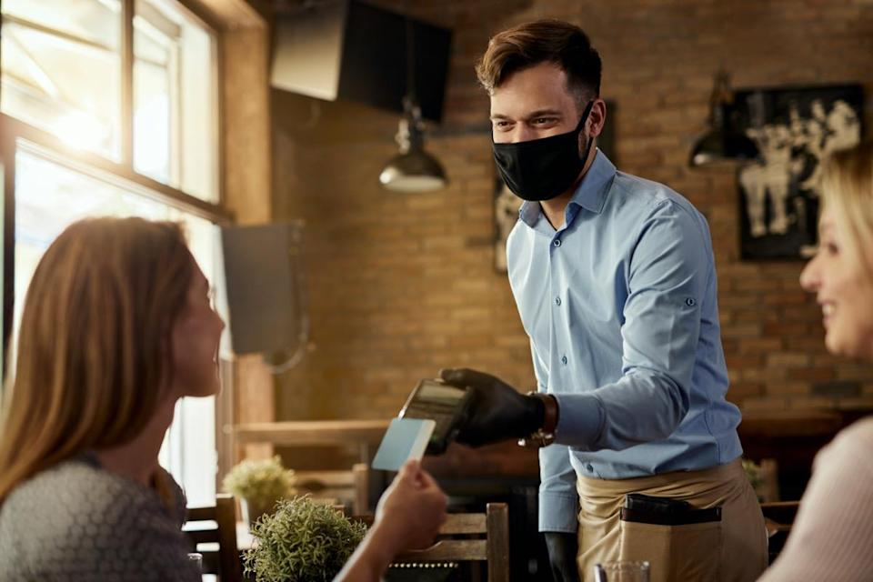 Female customer making contactless payment to a waiter who is wearing protective face mask in a cafe.