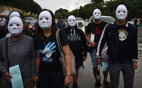 Protesters wearing masks depicting victims of extra judicial killings taking part in a demonstration against the killings of suspected drug users in Manila - Credit: AFP