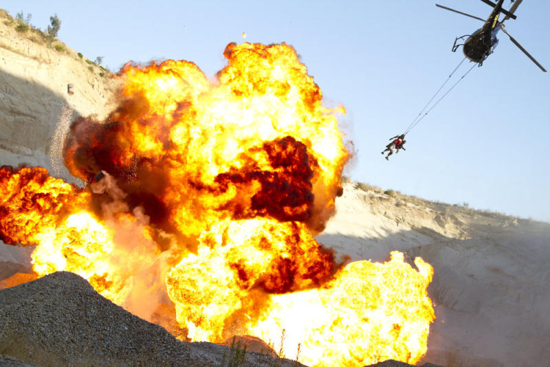 "In this image released by NBC, contestants are whisked to safety by a helicopter after completing a task in the ""Heli Truck TNT Crash"" stunt in the premiere episode  of ""Fear Factor,"" airing Monday, Dec. 12, 2011, on NBC. (AP Photo/NBC, Michael Weaver)"