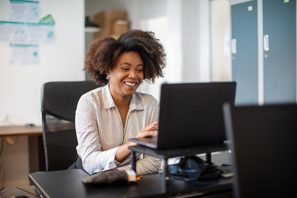 African american businesswoman working in office having a video conference. Smiling female executive sitting at her desk making a video call with laptop in office.
