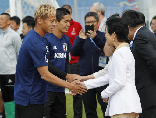 Japan's Princess Takamado, right, and Japan's Keisuke Honda, left, shake hands prior to a training session of Japan national team at the 2018 soccer World Cup in Kazan, Russia, Thursday, June 21, 2018. (AP Photo/Eugene Hoshiko)