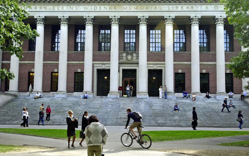 Students pass in front of Harvard's Widener Library