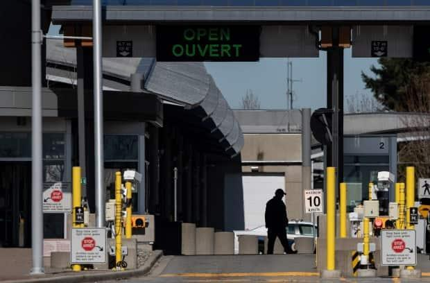 A Canada Border Services Agency officer is silhouetted at the Douglas-Peace Arch border crossing in Surrey, B.C.  (Darryl Dyck/Canadian Press - image credit)