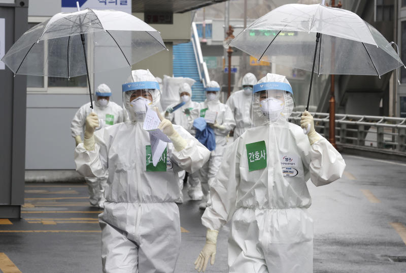Medical staff members arrive for a duty shift at Dongsan Hospital in Daegu, South Korea, Friday, March 27, 2020. The new coronavirus causes mild or moderate symptoms for most people, but for some, especially older adults and people with existing health problems, it can cause more severe illness or death.(Lee Yong-hwan/Newsis via AP)