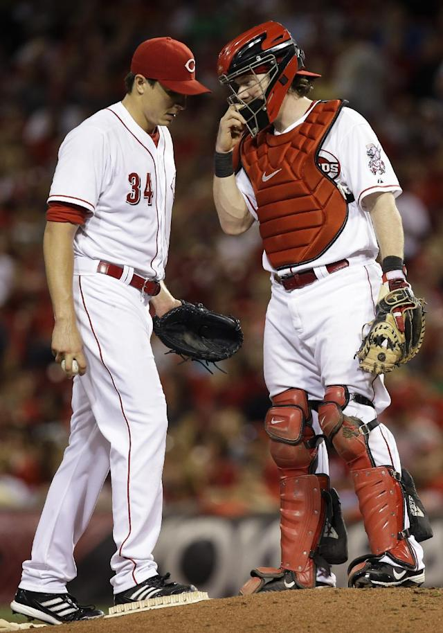 Cincinnati Reds starting pitcher Homer Bailey (34) talks with catcher Ryan Hanigan in the sixth inning of a baseball game against the St. Louis Cardinals, Tuesday, Sept. 3, 2013, in Cincinnati. (AP Photo/Al Behrman)