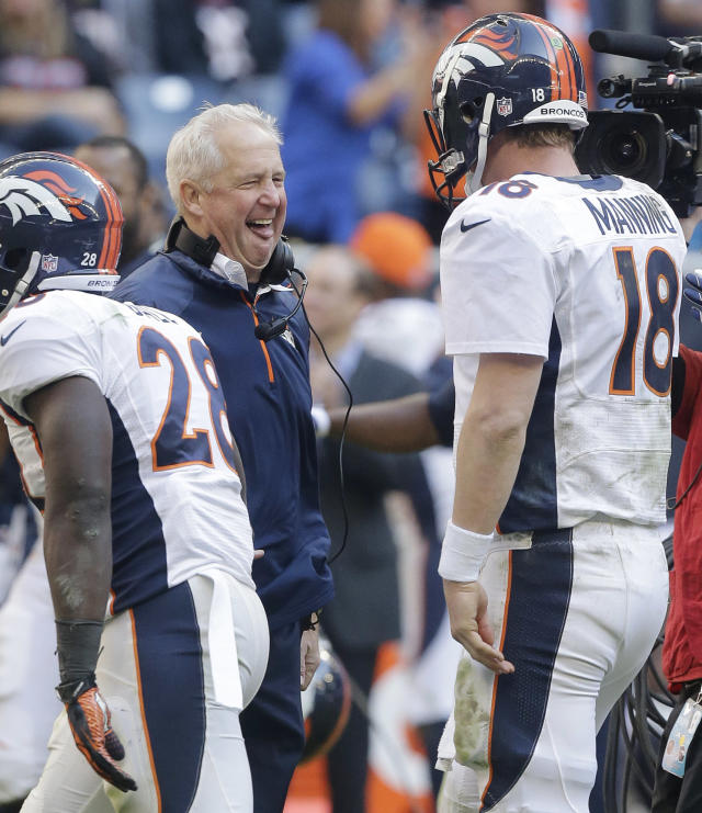 Denver Broncos coach John Fox, center, celebrates with Peyton Manning (18) after Manning threw a touchdown pass during the fourth quarter of an NFL football game against the Houston Texans, Sunday, Dec. 22, 2013, in Houston. (AP Photo/Patric Schneider)