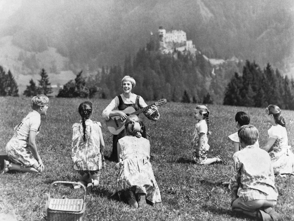 <p>Julie Andrews, portraying Maria von Trapp in<em> The Sound of Music</em>, sings to her charges while sitting in a pasture</p>