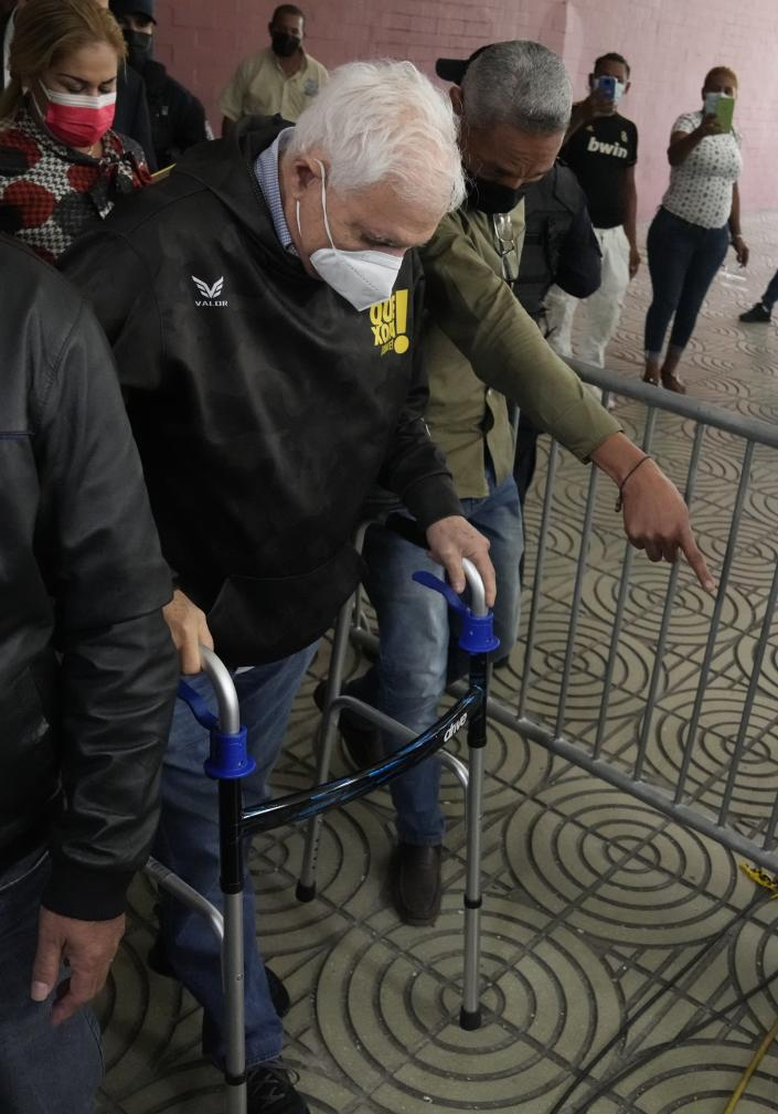 Panama's former President Ricardo Martinelli exits a court using a walker at the end of the first day of his trial, in Panama City, Wednesday, July 21, 2021. Martinelli is charged with political espionage during his administration, the same case for which he was acquitted in 2018. (AP Photo/Arnulfo Franco)
