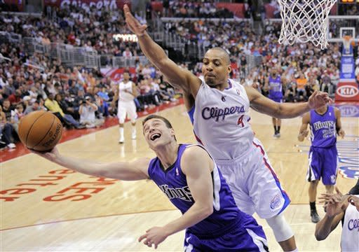 Sacramento Kings guard Jimmer Fredette, left, shoots under pressure from Los Angeles Clippers guard Randy Foye during the first half of their NBA basketball game, Saturday, April 7, 2012, in Los Angeles. (AP Photo/Mark J. Terrill)