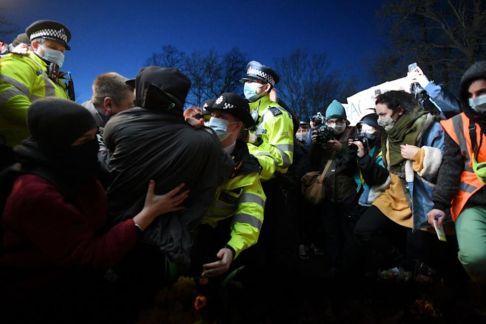 Police officers scuffle with people gathering at a band-stand where a planned vigil in honour of murder victim Sarah Everard was cancelled after police outlawed it due to Covid-19 restrictions, on Clapham Common, south London on March 13, 2021, - The police officer charged with murdering young Londoner, Sarah Everard, who disappeared while walking home from a friend's house, appeared in court on March 13, 2021, as organisers cancelled a vigil in her honour due to coronavirus restrictions. (Photo by JUSTIN TALLIS / AFP) (Photo by JUSTIN TALLIS/AFP via Getty Images)