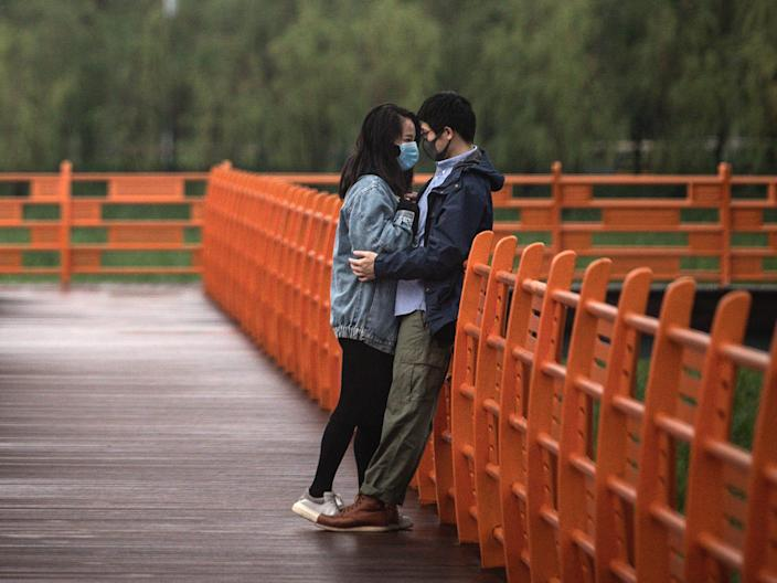 A couple hug in Jiangtan park after its re-opening on March 26, 2020 in Wuhan, Hubei province, China.
