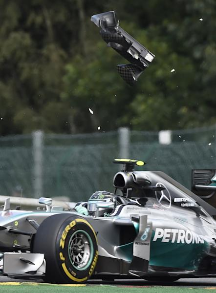 A pice of wing flys over Mercedes-AMG's German driver Nico Rosberg after a collision with teammate Mercedes-AMG's British driver Lewis Hamilton at the Spa-Francorchamps ciruit in Spa on August 24, 2014 during the Belgium Formula One Grand Prix (AFP Photo/Johan Thys)