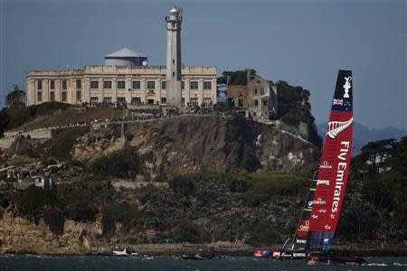 Oracle Team USA crosses the finish line ahead of Emirates Team New Zealand to win Race 17 of the 34th America's Cup yacht sailing race in San Francisco, California September 24, 2013. REUTERS/Stephen Lam