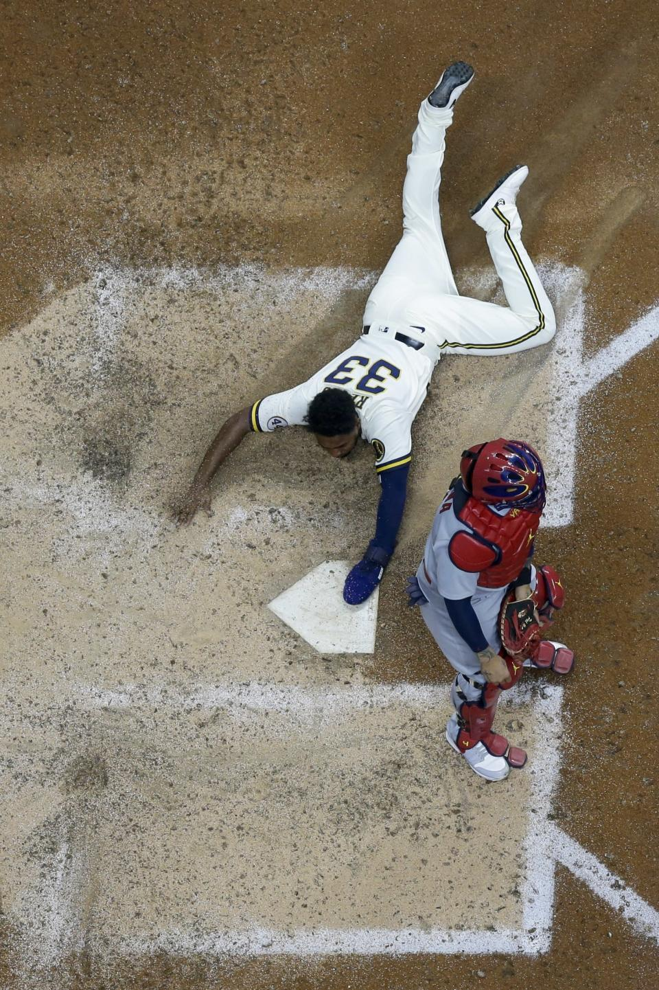 Milwaukee Brewers' Pablo Reyes scores past St. Louis Cardinals catcher Yadier Molina during the eighth inning of a baseball game Wednesday, May 12, 2021, in Milwaukee. Reyes scored from first on a double by Travis Shaw. (AP Photo/Morry Gash)