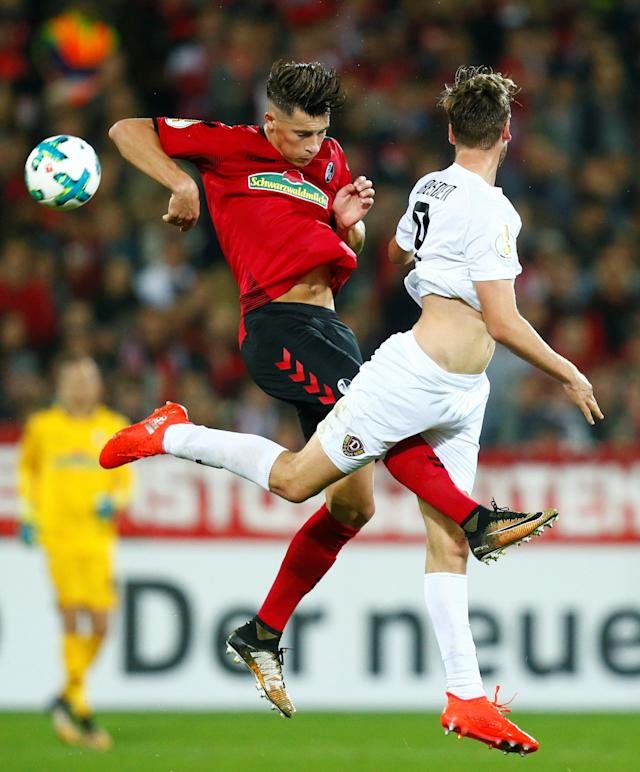 Soccer Football - DFB Cup Second Round - SC Freiburg v Dynamo Dresden - Dreisamstadion, Freiburg, Germany - October 25, 2017 SC Freiburg's Robin Koch in action with Dynamo Dresden's Lucas Roser REUTERS/Ralph Orlowski DFB RULES PROHIBIT USE IN MMS SERVICES VIA HANDHELD DEVICES UNTIL TWO HOURS AFTER A MATCH AND ANY USAGE ON INTERNET OR ONLINE MEDIA SIMULATING VIDEO FOOTAGE DURING THE MATCH.