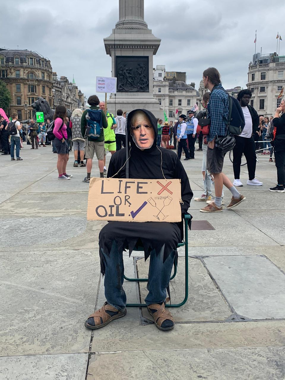 A man wearing a Boris Johnson face mask holds an anti-fossil fuel placard in Trafalgar Square (Sam Hancock/The Independent)
