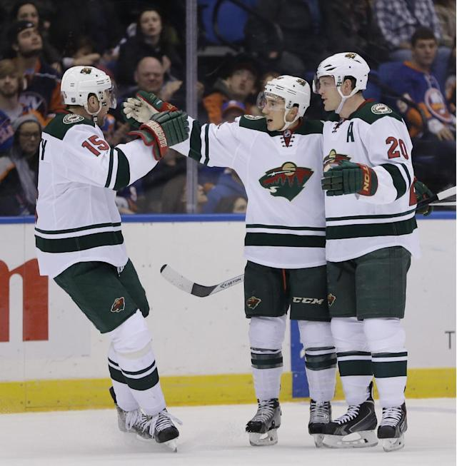 Minnesota Wild's Jared Spurgeon, center, celebrates his goal with teammates Dany Heatley, left, and Ryan Suter during the first period of the NHL hockey game against the New York Islanders, Tuesday, March 18, 2014, in Uniondale, New York. (AP Photo/Seth Wenig)