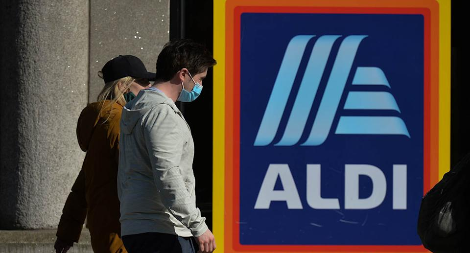 People walk past an Aldi sign. Source: Getty Images