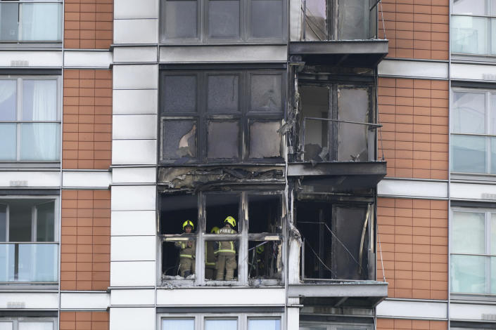 Firefighters inspect damage to a 19-storey tower block in New Providence Wharf in London, Friday, May 7, 2021. Firefighters have tacked a blaze in a London apartment tower that has cladding similar to that used on a building where 72 people died in 2017. London Fire Brigade said about 125 firefighters tackled a fire on Friday that spread to three floors of a 19-story building in the city's docklands. (Yui Mok/PA via AP)