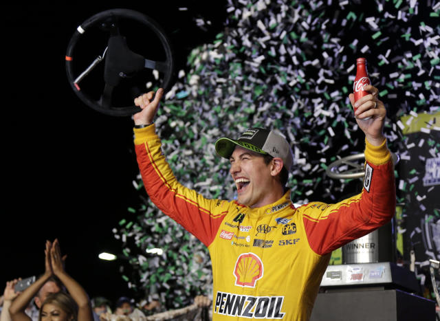 Joey Logano waves his steering wheel as confetti flies after winning the NASCAR Cup Series Championship auto race at the Homestead-Miami Speedway, Sunday, Nov. 18, 2018, in Homestead, Fla. (AP Photo/Terry Renna)