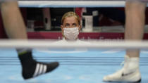 <p>A masked ring side official watches as Azerbaijan's Mahammad Abdullayev, right, and Bahrain's Danis Latypov compete in a men's super heavyweight over 91-kg boxing match at the 2020 Summer Olympics in Tokyo, Japan. (AP Photo/David Goldman)</p>
