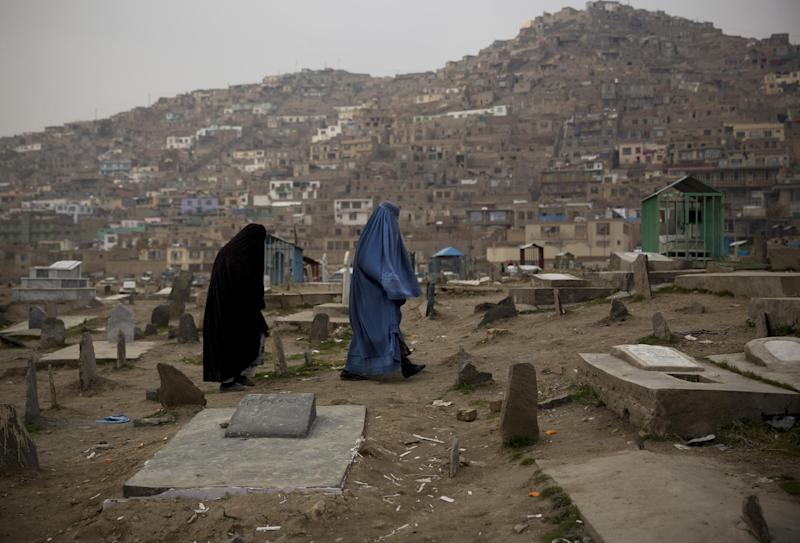 In this Friday, March 7, 2014 photo, Afghan women cross a cemetery in the center of Kabul, Afghanistan. A gender and development specialist and human rights activist, Afghan Wazhma Frogh says her experience characterizes the women's rights movement in her country- after 12 years, billions of dollars and countless words emanating from the West commiserating with Afghan women, the successes are fragile, the changes superficial and vulnerable. (AP Photo/Anja Niedringhaus)