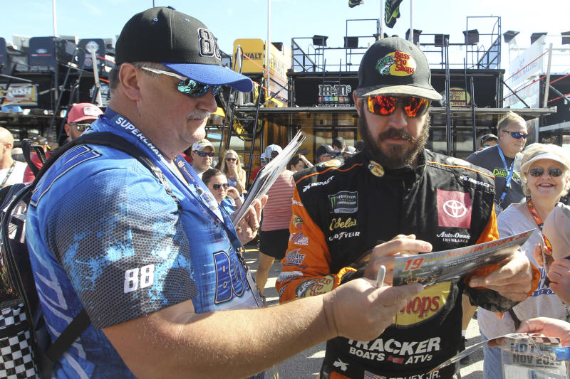 Martin Truex Jr. signs autographs as he enters the garage for a NASCAR Cup Series auto race practice at Homestead-Miami Speedway in Homestead, Fla., Saturday, Nov. 16, 2019. (AP Photo/Luis M. Alvarez)
