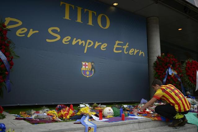 "A man places flowers for pay his respect to late former FC Barcelona's coach Tito Vilanova at Camp Nou Stadium in Barcelona, Spain, Saturday, April 26, 2014. FC Barcelona announced on their web page Friday April 25, 2014 that Vilanova has died Friday following a long battle with throat cancer. He was 45. The banner reads in Catalan: ""Tito Forever eternal"". (AP Photo/Manu Fernandez)"
